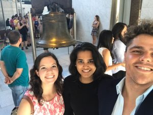Three smiling students in front of historic Liberty Bell in Philadelphia USA