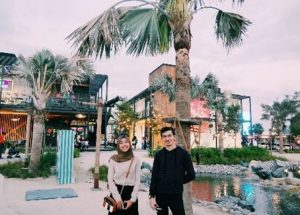 Smiling young woman and young man by palm trees shops and restaurants