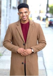 Young man in a wool coat smiling