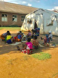 villagers sitting around a tent